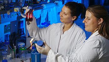 Darstellung zweier Frauen in einem biologischen Labor mit weissen Kitteln.